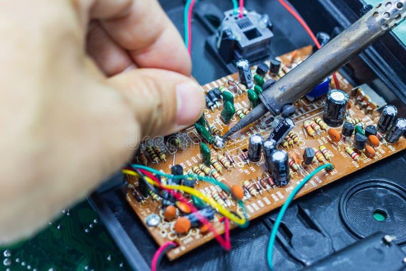 Reparação do técnico eletrônica da placa de circuito do ` s do computador por ferros de solda imagens de stock