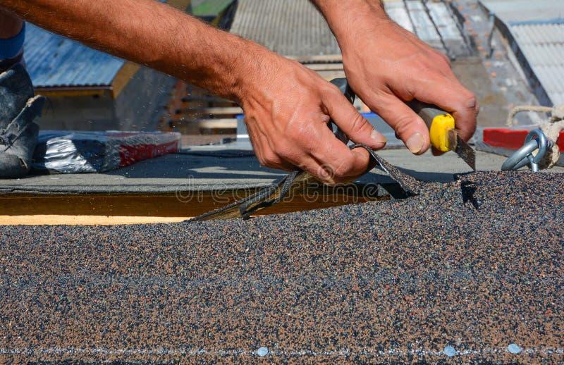 Reparação do telhado cortando telhas de feltro ou de betume durante trabalhos waterproofing fotografia de stock