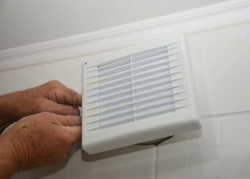 Reparação do ventilador do banho, instalação Handyman instalando novo ventilador de ventilação, sistema de ventilação no banheiro imagem de stock