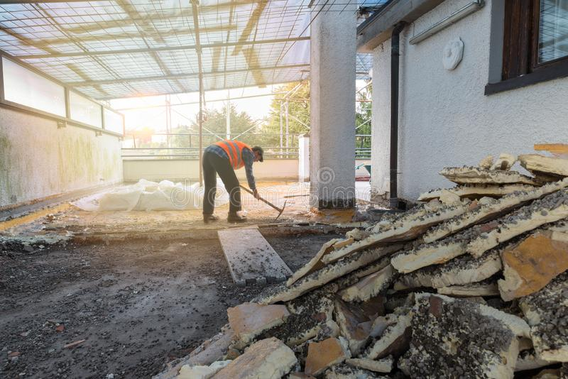 """Reparación casera Reconstruyendo la impermeabilización y el aislamiento tejado de un †de la terraza """" Trabajador retroiluminado foto de archivo libre de regalías"""