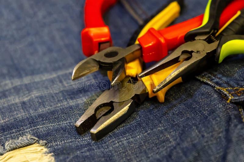 Reparación de goma amarilla roja de la construcción de la herramienta de los apretones de las pinzas del hierro en fondo de los t imágenes de archivo libres de regalías