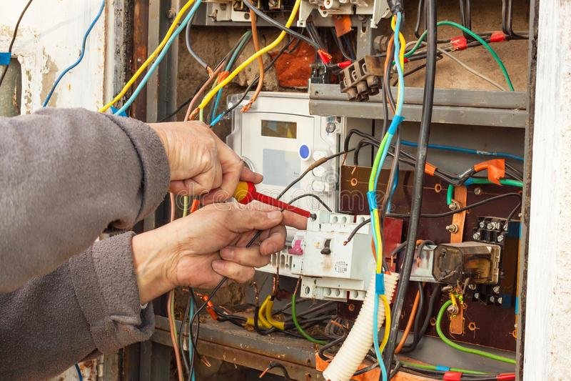 Reparación de la distribución de la electricidad en una casa vieja El hombre repara la centralita telefónica fotografía de archivo