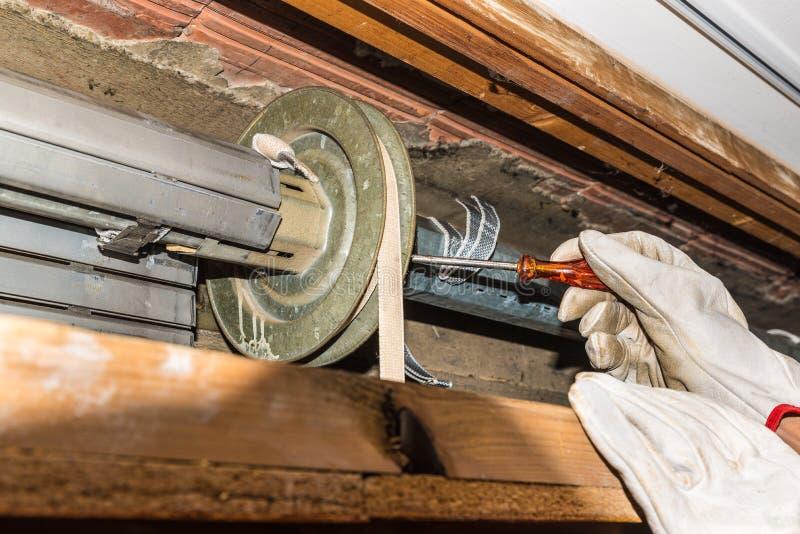 Reparación de la persiana enrrollable El trabajador ajusta un obturador quebrado del rodillo de un hogar foto de archivo