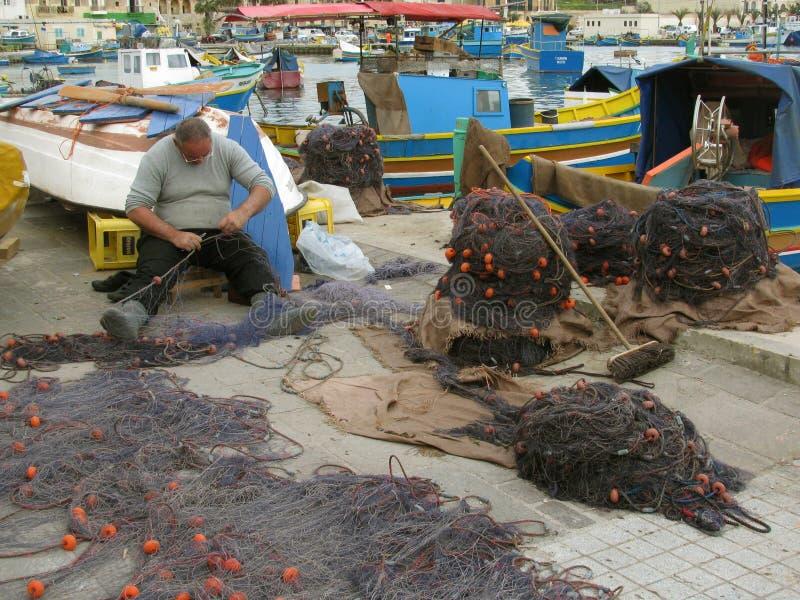 Reparación de las redes de pesca en el puerto malta Marsachlokk fotos de archivo
