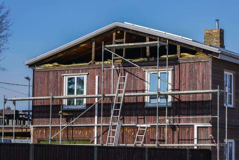 Reparaci?n de madera de dos pisos de la casa de estancia, aislamiento t?rmico del ?tico imagen de archivo libre de regalías