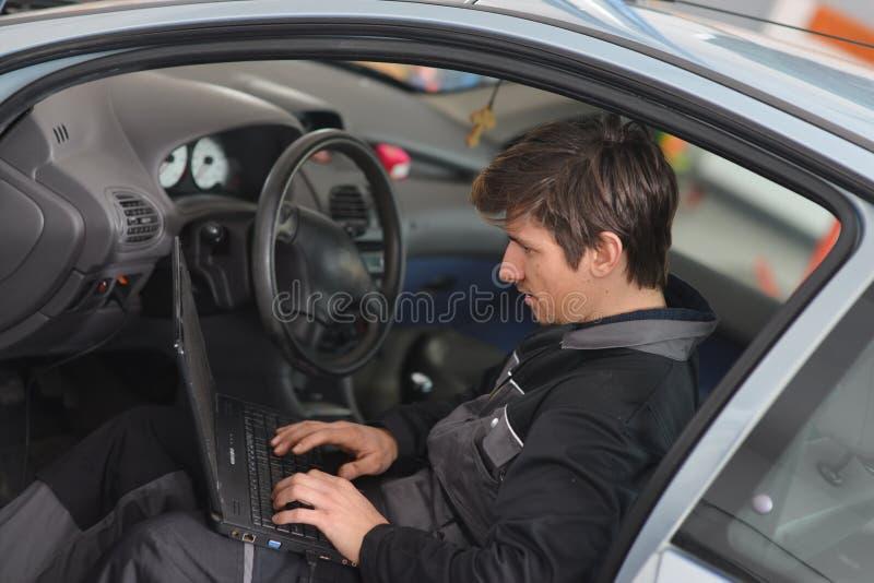 Reparación del coche con el ordenador fotografía de archivo