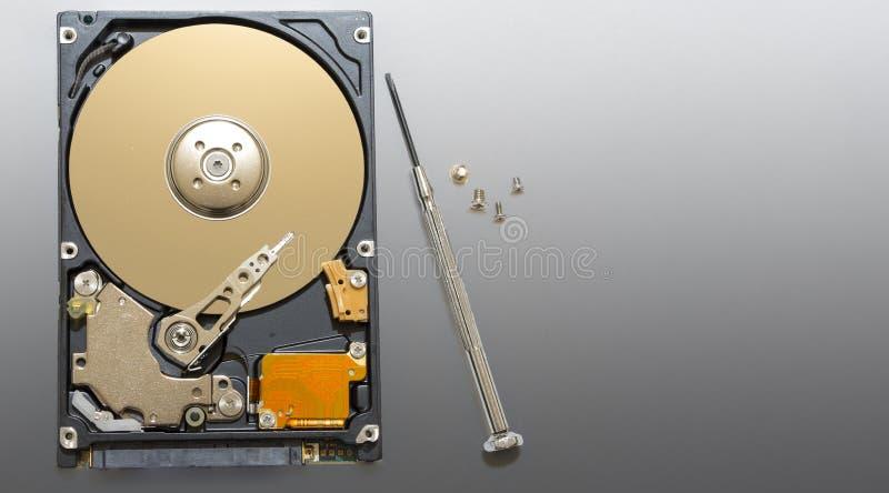 Reparación del disco duro, de los tornillos y de los destornilladores defectuosos en el banco fotos de archivo