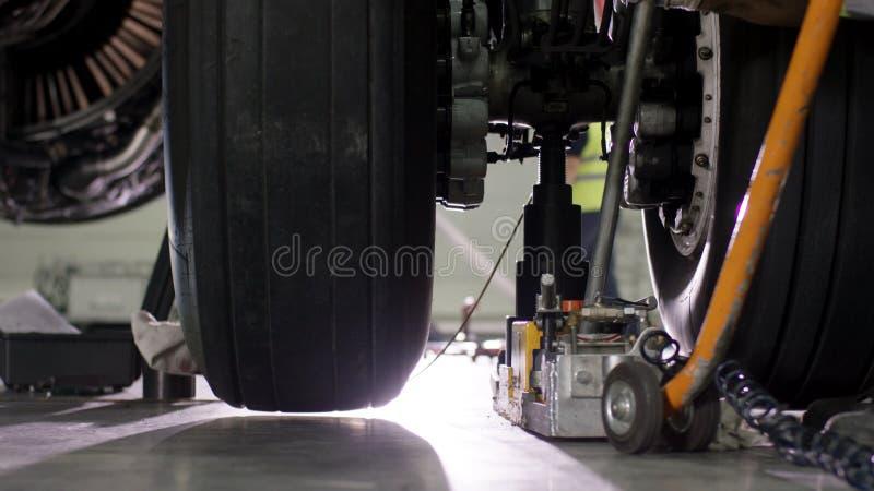 Reparación del freno de los aviones Ciérrese para arriba de la rueda y del eje del aeroplano Neumático enorme del aeroplano con e fotografía de archivo