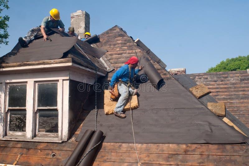 Reparación del tejado de los trabajadores emigrantes fotografía de archivo