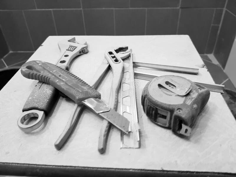 Reparación - edificio con las herramientas llave, cuchillo, cuchillo del hierro, llave ajustable y cinta métrica en un taburete foto de archivo libre de regalías