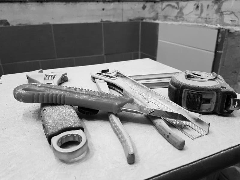 Reparación - edificio con las herramientas llave, cuchillo, cuchillo del hierro, llave ajustable y cinta métrica en un taburete fotos de archivo libres de regalías