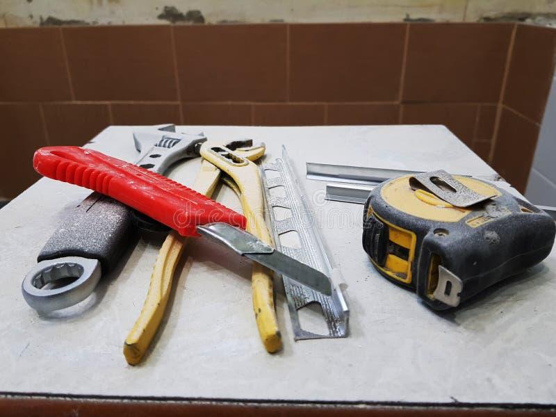 Reparación - edificio con las herramientas llave, cuchillo, cuchillo del hierro, llave ajustable y cinta métrica en un taburete fotografía de archivo libre de regalías