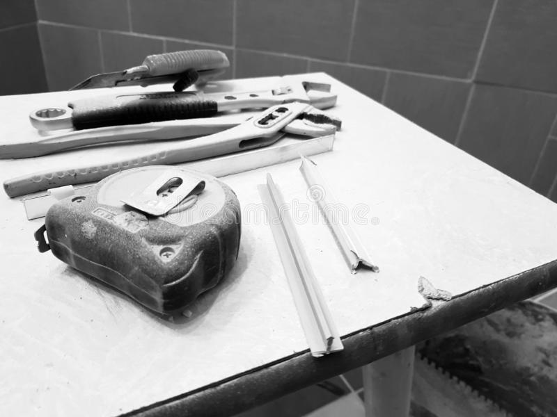 Reparación - edificio con las herramientas llave, cuchillo, cuchillo del hierro, llave ajustable y cinta métrica en un taburete imágenes de archivo libres de regalías