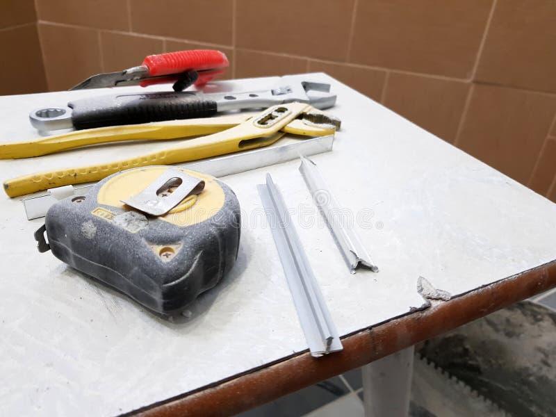 Reparación - edificio con las herramientas llave, cuchillo, cuchillo del hierro, llave ajustable y cinta métrica en un taburete fotos de archivo