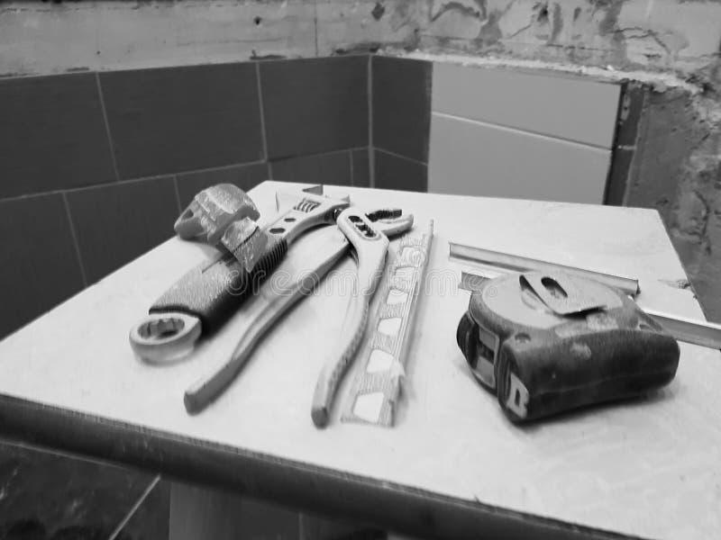 Reparación - edificio con las herramientas llave, cuchillo, cuchillo del hierro, llave ajustable y cinta métrica en un taburete imagenes de archivo