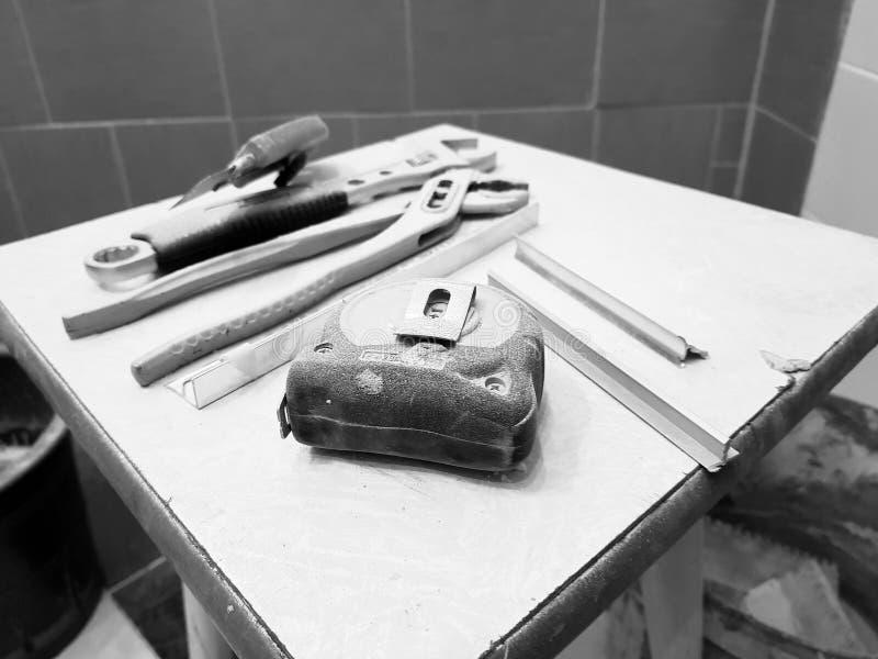 Reparación - edificio con las herramientas llave, cuchillo, cuchillo del hierro, llave ajustable y cinta métrica en un taburete foto de archivo