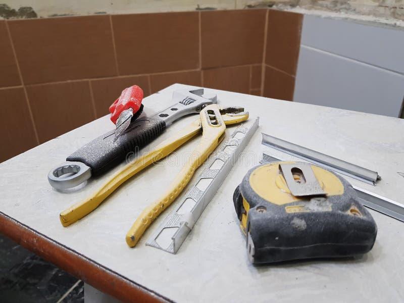 Reparación - edificio con las herramientas llave, cuchillo, cuchillo del hierro, llave ajustable y cinta métrica en un taburete fotografía de archivo