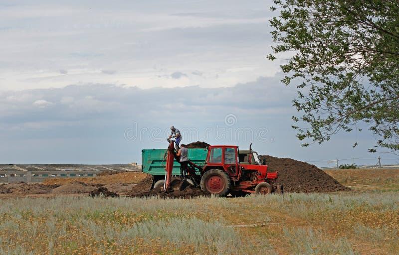 Reparación forzada del cubo-manipulante del ` s del tractor durante el cargamento de la tierra en el camión volquete en Erzovka foto de archivo
