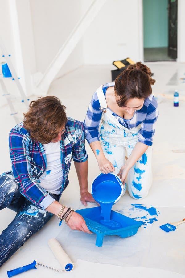 Reparación, renovación y concepto de la gente - los pares que van a pintar la pared, están preparando el color y los cepillos imagen de archivo