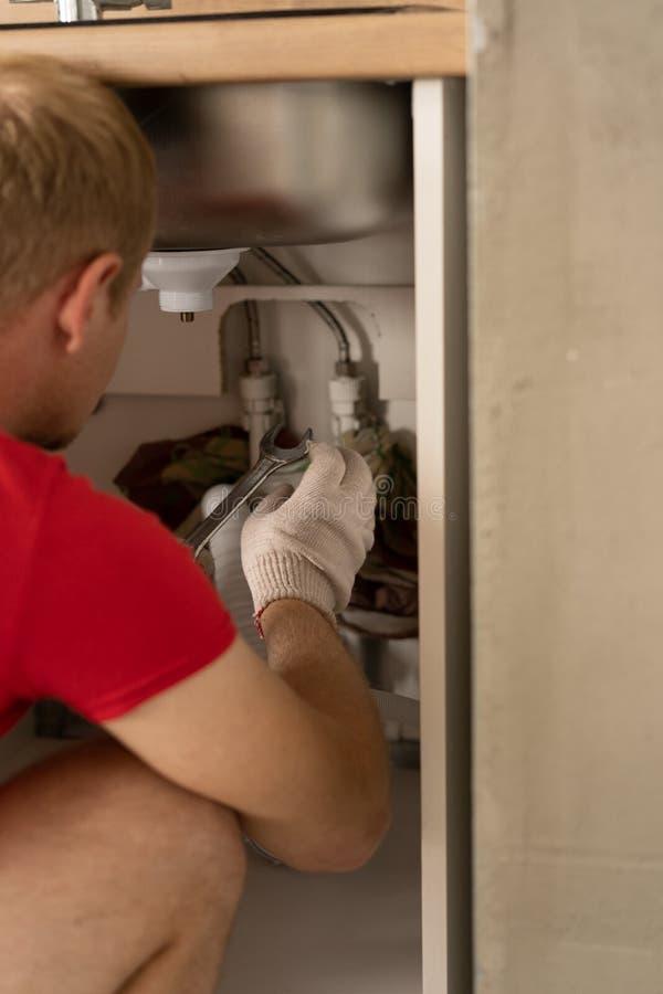 Reparaci?n y decoraci?n fontanero que repara los tubos de agua en la cocina debajo del fregadero fotos de archivo libres de regalías