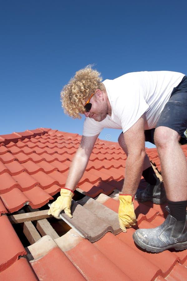 Reparaciones de techumbre de la teja del trabajador de construcción imagen de archivo libre de regalías