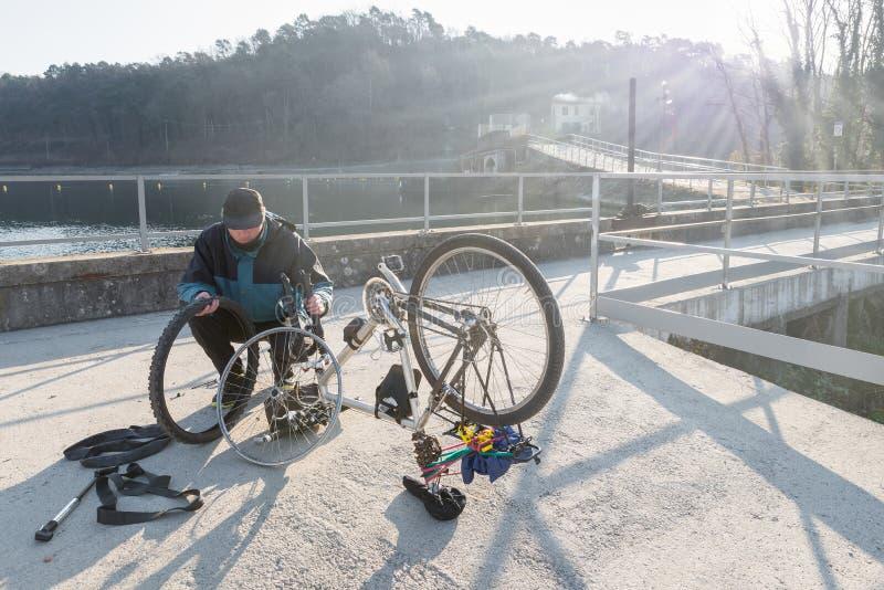 Reparaciones del hombre una bicicleta con el neumático desinflado Concepto de imprevisto imagen de archivo