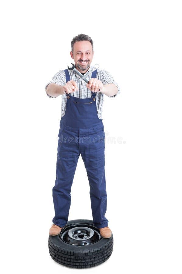 Reparador alegre na chave cruzada terra arrendada do pneu imagem de stock royalty free