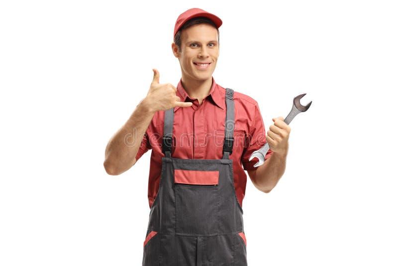 Reparador com uma chave que faz a uma chamada me gesto foto de stock royalty free
