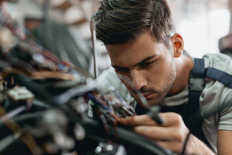 reparador considerável novo que trabalha com motocicleta imagens de stock royalty free