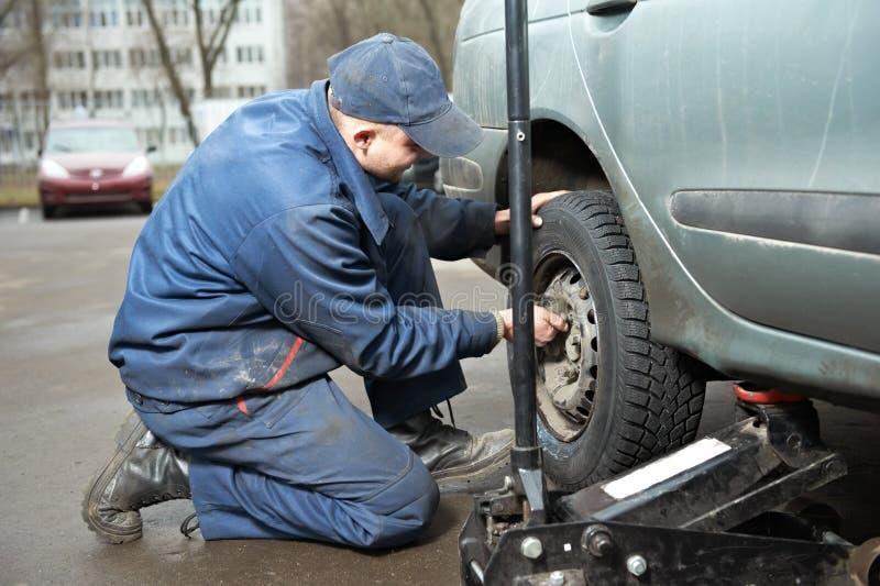 Reparador de Machanic en la guarnición del neumático con el gato del coche fotos de archivo