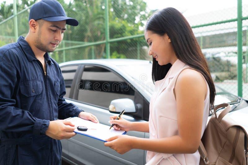 Reparador de Technicisn que dá a chave do carro à mulher no workshop Carro do cliente do reparo do mecânico da oficina na auto  imagem de stock