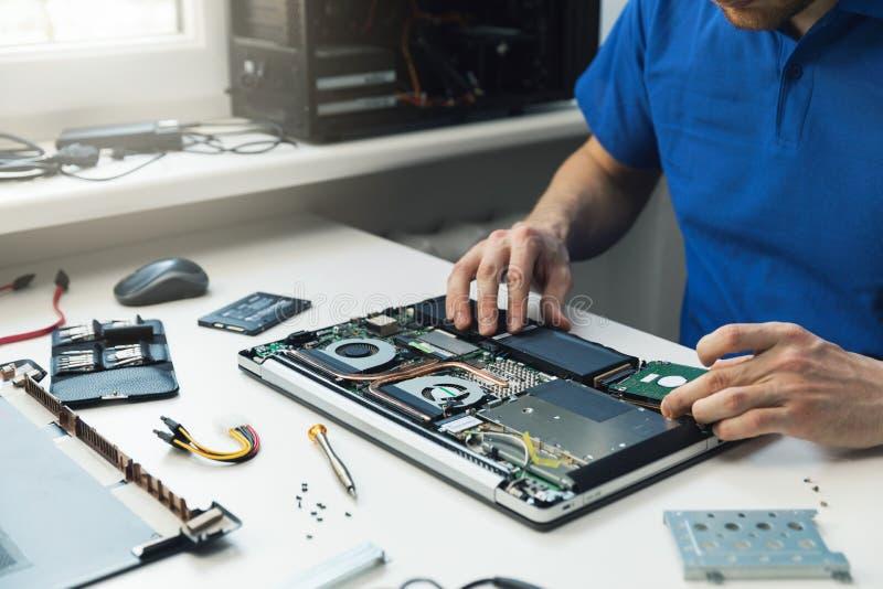 Reparador del ordenador que instala la nueva unidad de disco duro en ordenador portátil imagen de archivo
