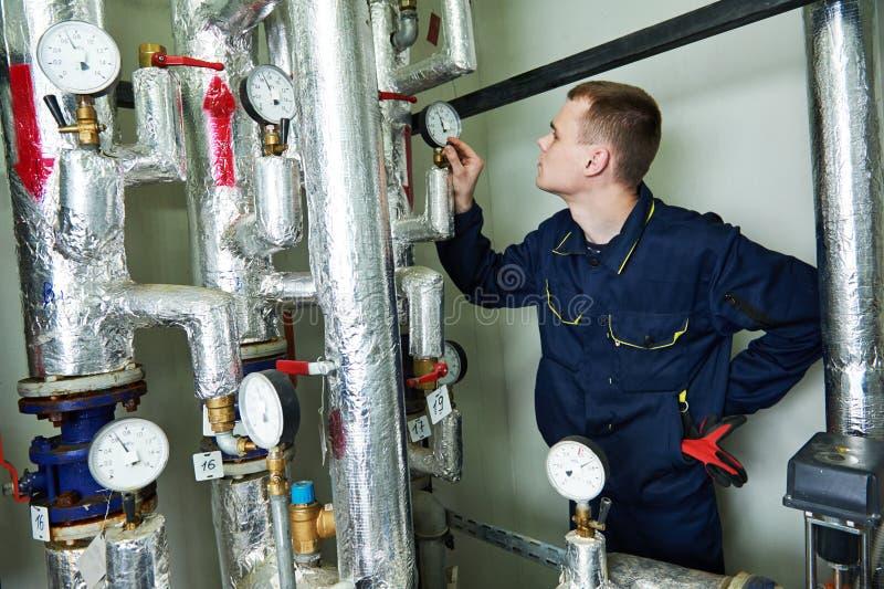 Reparador do coordenador do aquecimento na sala de caldeira imagem de stock