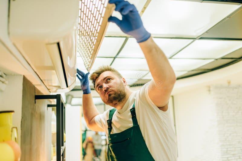 Reparador en reparaciones uniformes el aire acondicionado foto de archivo libre de regalías