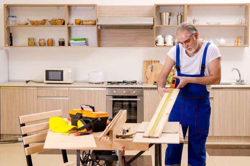 Reparador envelhecido do contratante que trabalha na cozinha imagem de stock
