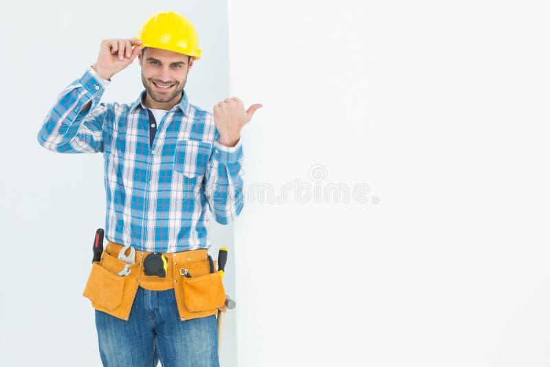Reparador feliz que señala hacia la cartelera en blanco imagenes de archivo