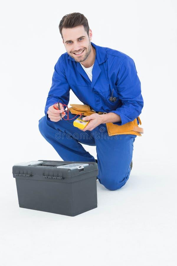 Reparador feliz que se arrodilla por la caja de herramientas fotografía de archivo