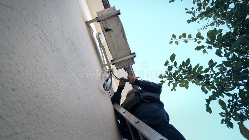 Reparador joven de la reparación del aire acondicionado en el sistema de aire acondicionado de fijación de la escalera imagenes de archivo