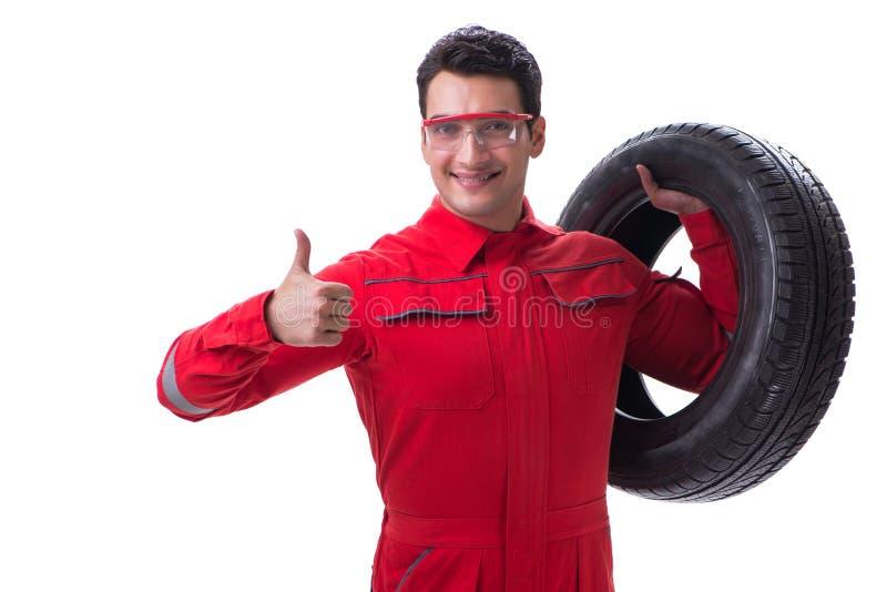 Reparador joven del neumático en las batas rojas aisladas en el backgrou blanco fotos de archivo libres de regalías