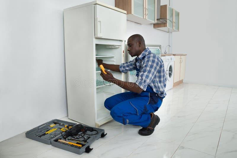 Reparador joven Repairing Refrigerator fotos de archivo