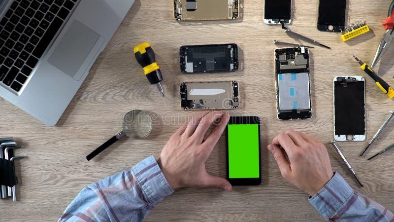 Reparador masculino que gira sobre o smartphone com a tela verde que verifica o após a fixação fotografia de stock
