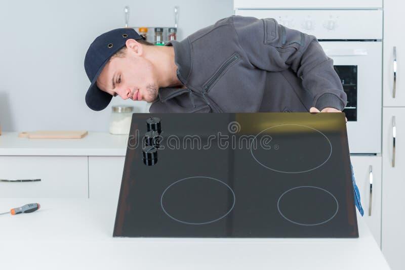 Reparador novo que instala dispositivos em clientes em casa imagens de stock