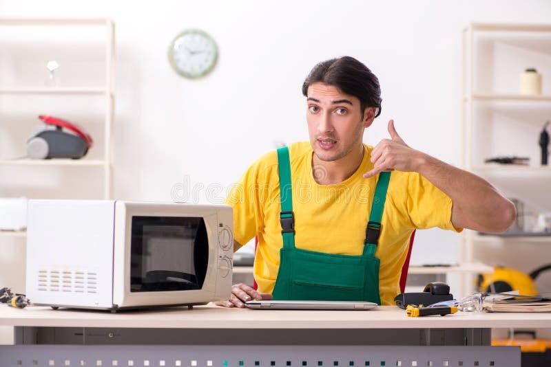 Reparador novo que repara a micro-ondas no centro de servi?o fotos de stock