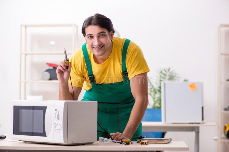 Reparador novo que repara a micro-ondas no centro de servi?o fotografia de stock royalty free