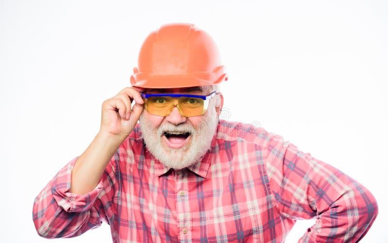 Reparador profesional en casco reparación y arreglo del arquitecto carrera del trabajador del ingeniero hombre barbudo maduro en  imagen de archivo