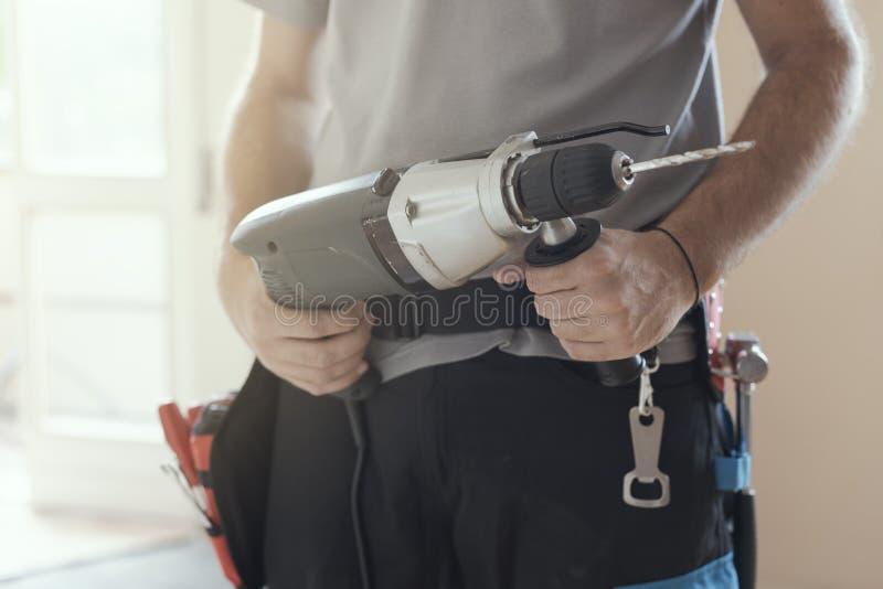 Reparador profissional que trabalha com uma broca foto de stock