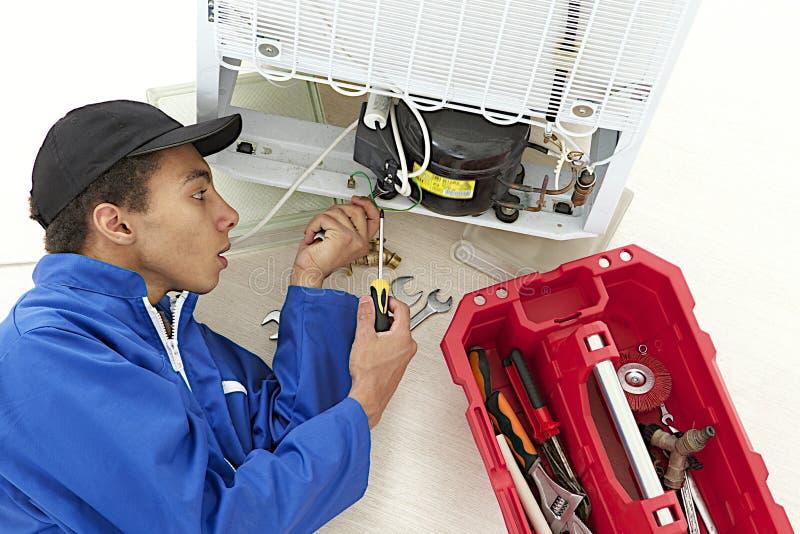 Reparador que faz a manutenção sobre um refrigerador fotografia de stock royalty free