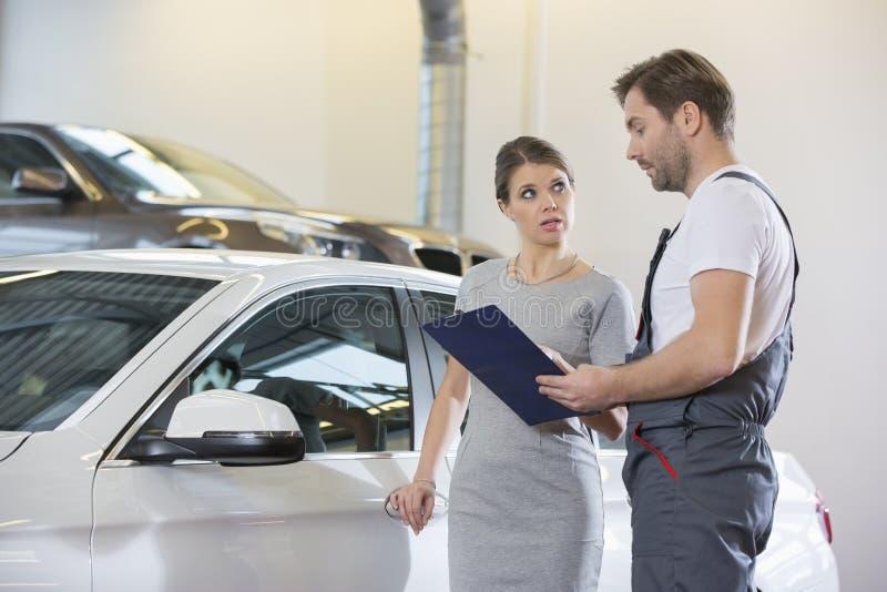 Reparador que guarda a prancheta ao conversar com o cliente fêmea na oficina de reparações do automóvel fotos de stock royalty free