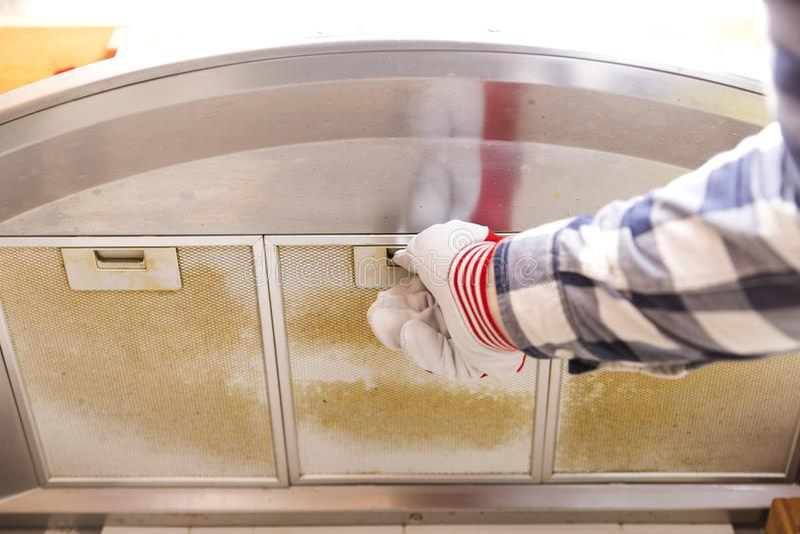Reparador que saca el filtro de malla de aluminio asqueroso de la cocina h fotografía de archivo libre de regalías