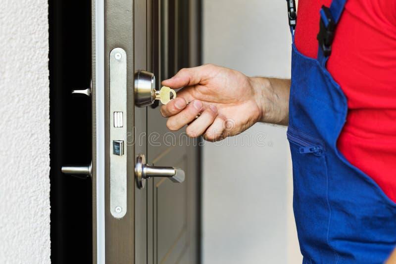 Reparador que trabalha com fechadura da porta imagem de stock royalty free